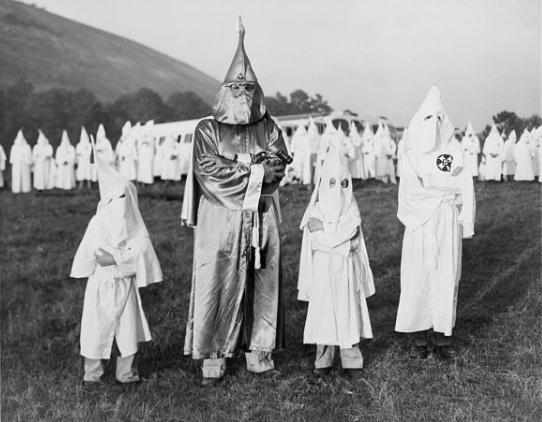 Razzismo nello sport. Georgia: tre bambini indossano l'uniforme bianca del Ku Klux Klan insieme al Dr. Samuel Green, Grand Dragon dell'organizzazione.