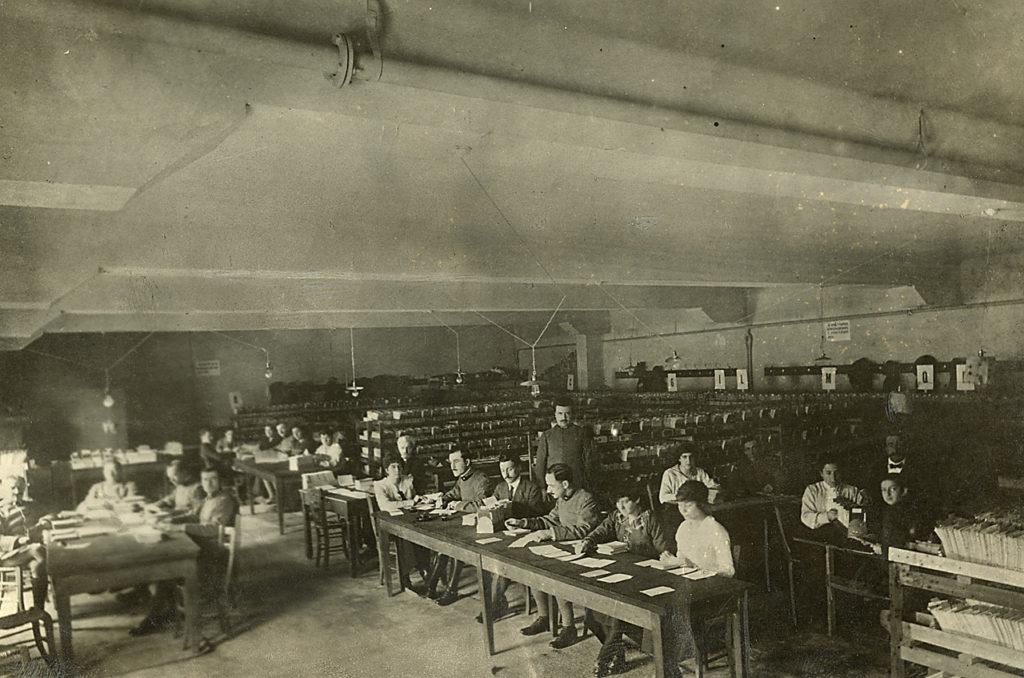 Scrivere la Grande Guerra. Donne e uomini al lavoro in un ufficio postale durante la Grande Guerra. Foto Archivio Touring Club Italiano [CC BY-SA 3.0]