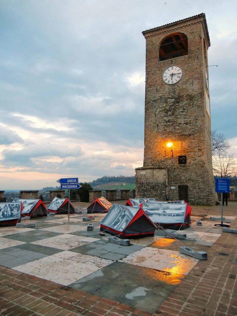 """Oltre i confini. Piazza Roma con le tende di """"Scappare la guerra camp"""", installazione realizzata in collegamento alla mostra fotografica di Luigi Ottani"""