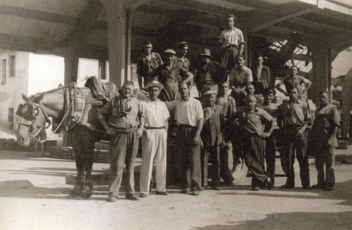 Storia di Vignola. La carovana facchini del mercato ortofrutticolo di Vignola in una foto del maggio 1945. Si stanno ancora rimuovendo le macerie dei bombardamenti aerei, eppure si riparte. Foto archivio Gruppo Mezaluna-Mario Menabue