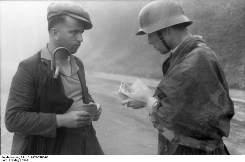 Un soldato tedesco controlla i documenti a un civile italiano. Mario Ricci