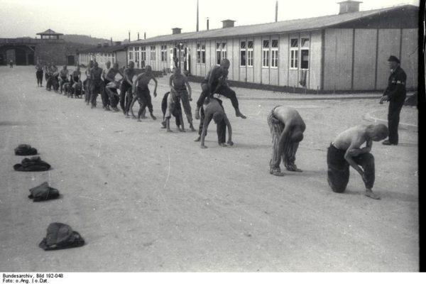Nel campo di concentramento di Mauthausen i prigionieri sono costretti a svolgere esercizi ginnici sotto la sorveglianza di un kapò. Bundesarchiv, Bild 192-048 / CC-BY-SA 3.0 - sport e Resistenza