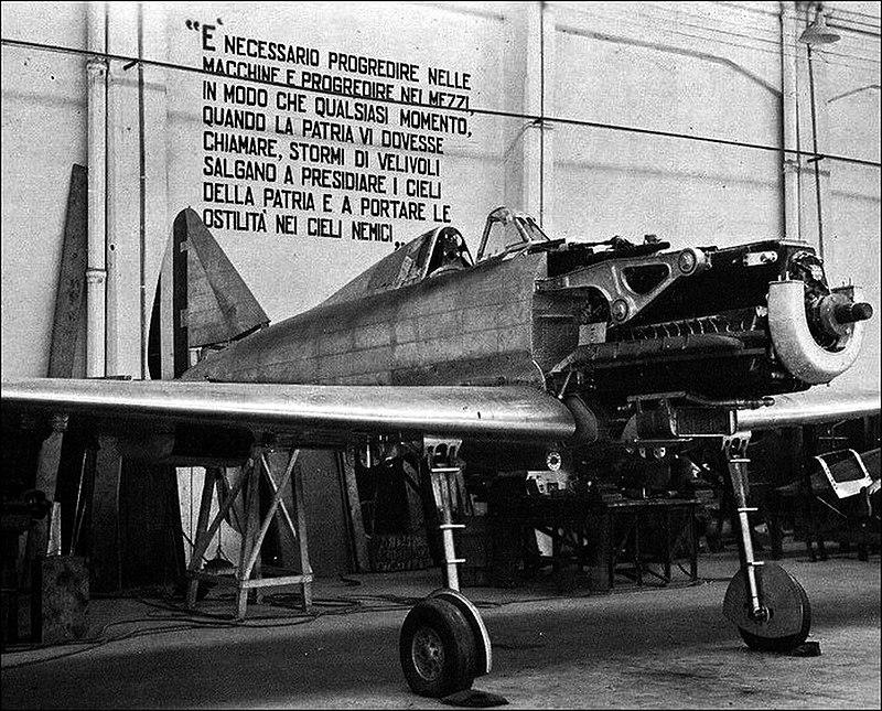 Primo prototipo dell'aereo da caccia RE.2001, prodotto alle Officine Reggiane all'inizio della Seconda guerra mondiale. Dietro l'aereo si nota un proclama di Benito Mussolini - contro la guerra