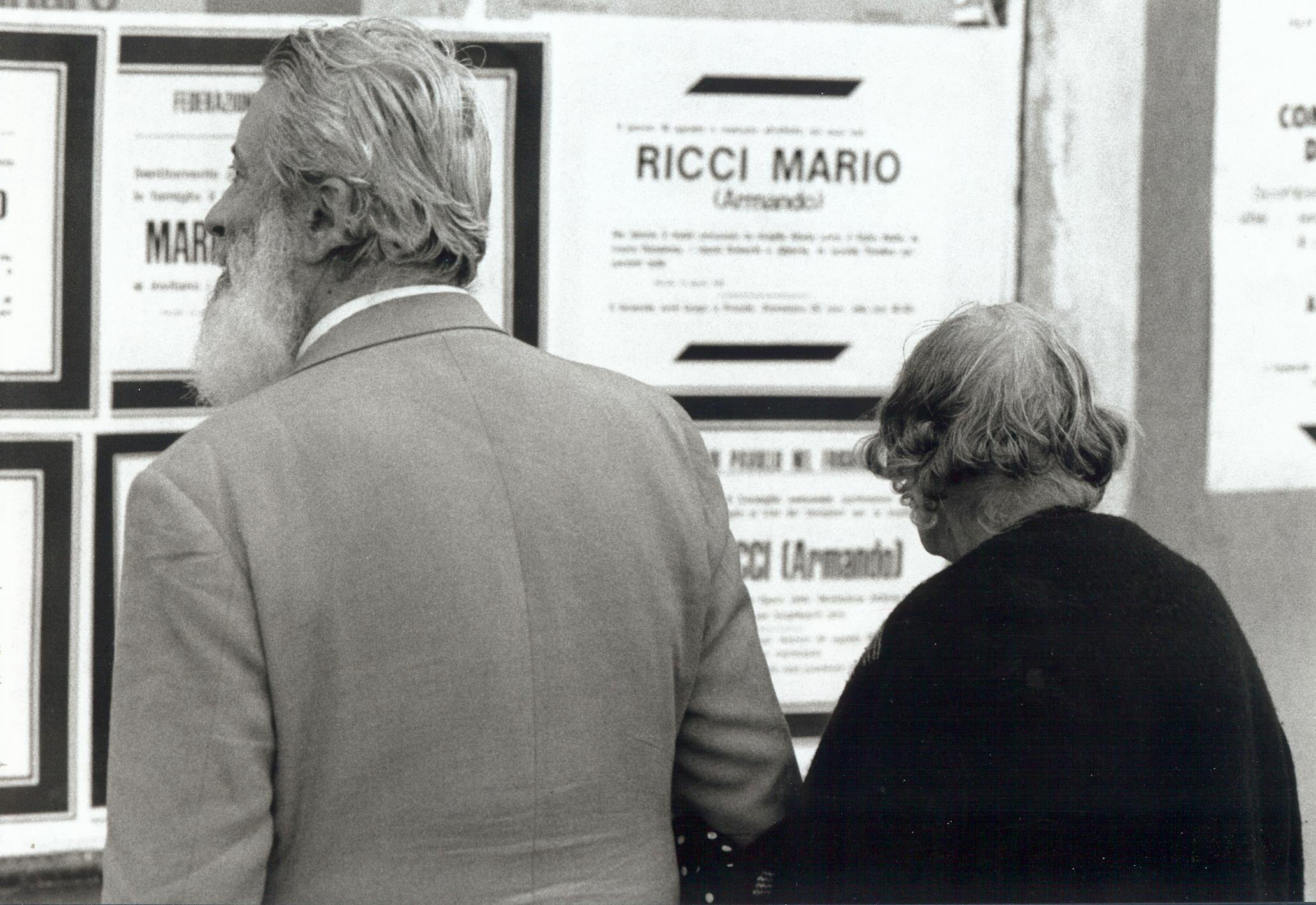 """Anziani osservano gli annunci mortuari di Mario Ricci. Foto tratta dalla mostra Mario Ricci """"Armando"""" dal mito alla storia - con Armando nel cuore"""