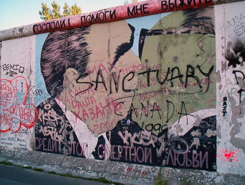 """caduta del muro di Berlino. Il murale rappresenta il dittatore sovietico Leonid Brežnev e il leader della DDR Erich Honecker mentre si baciano. La scritta in alto, in russo dice: """"Signore! Aiutami a sopravvivere a questo amore letale, ti prego"""". Foto di Victorgrigas via Wikimedia Commons"""