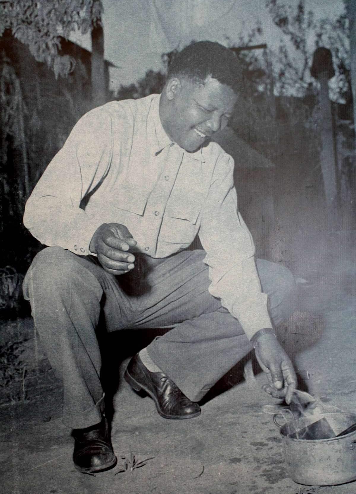 Nelson Mandela nel 1960, ritratto mentre brucia uno dei lasciapassare imposti ai neri dal governo sudafricano dell'apartheid