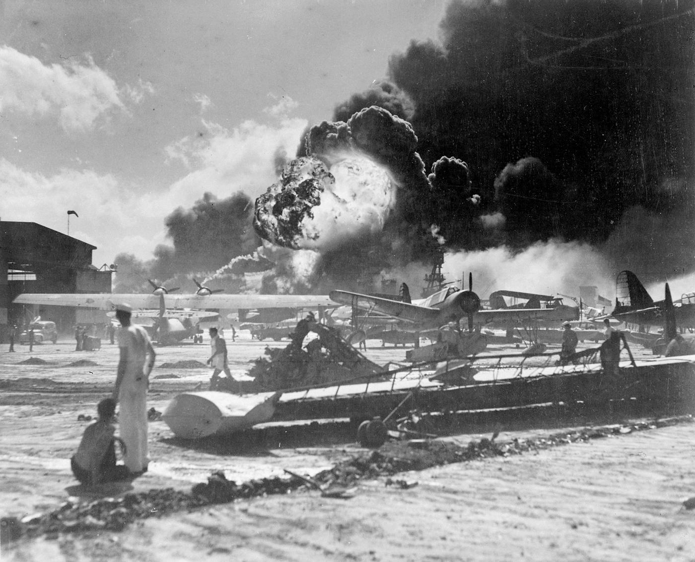 Aerei statunitensi danneggiati durante l'attacco di Pearl Harbor a Ford Island. Sullo sfondo si vede la nave USS Shaw in fiamme. USN - Official U.S. Navy photograph 80-G-19948